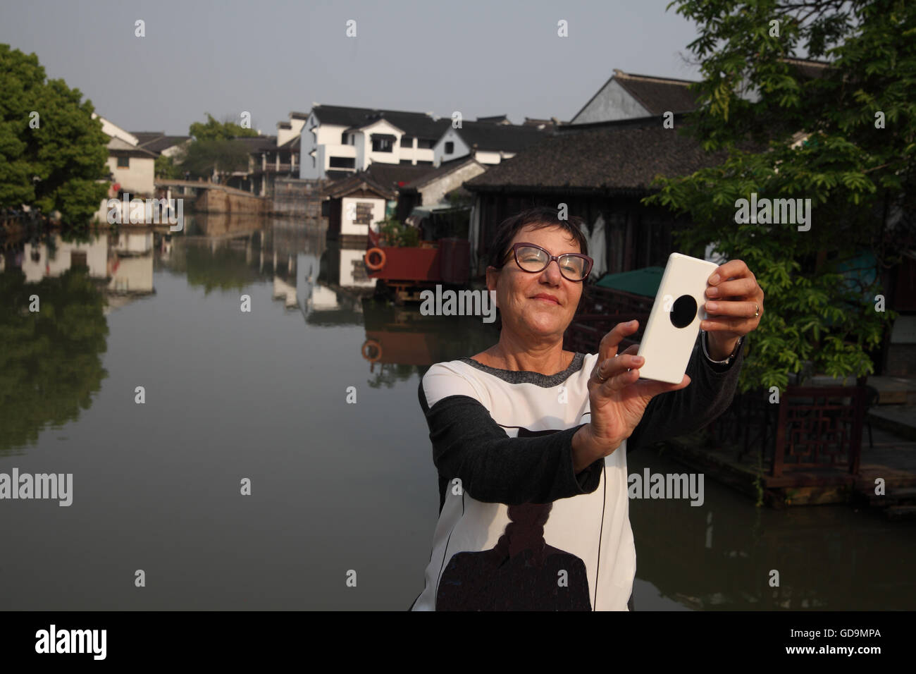 A 70 year old senior citizen Israeli woman, a tourist, is using her smartphone to take a selfie over Tongli's - Stock Image
