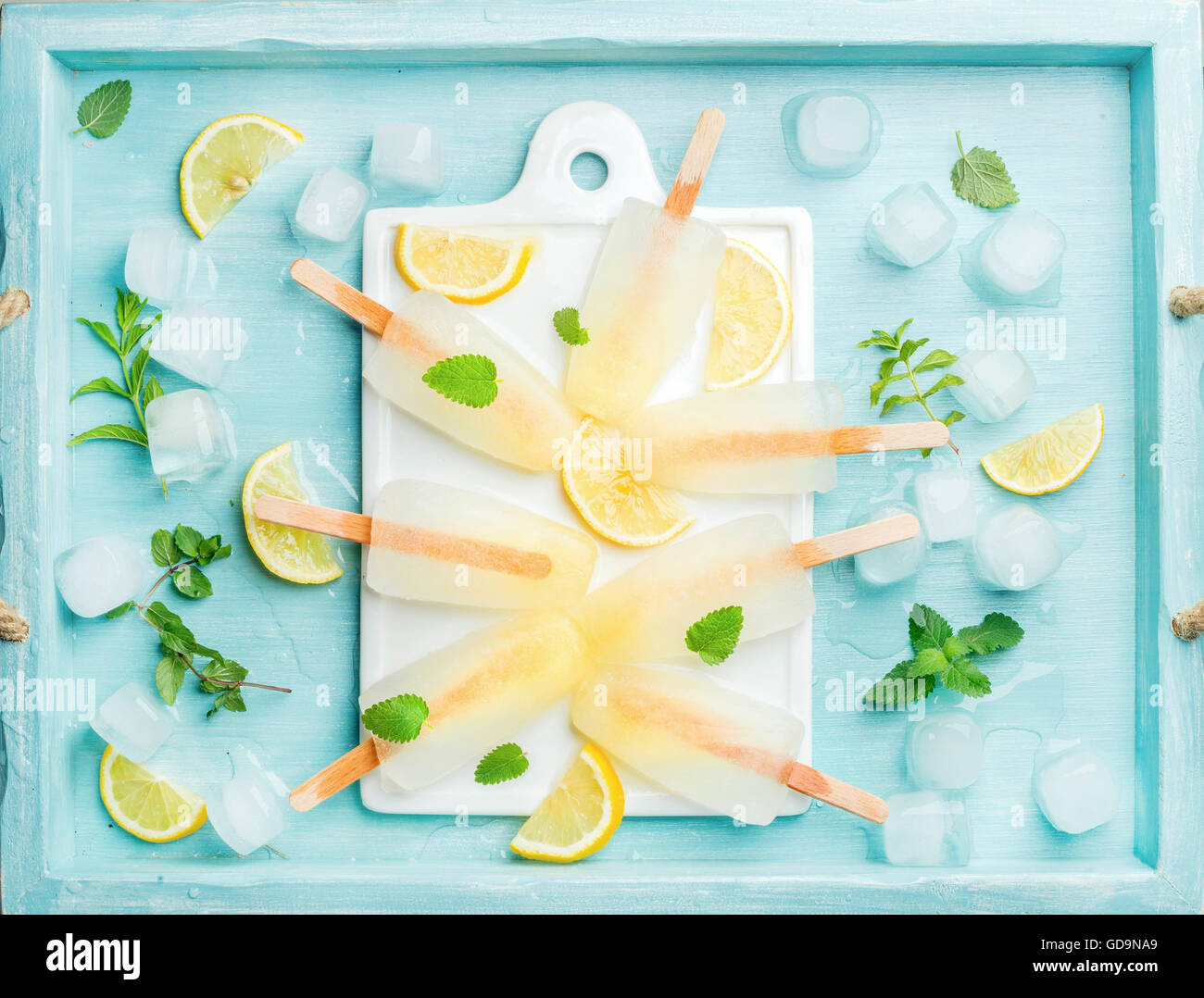 Lemon ice lollies on white ceramic board served with lemon slices, ice cubes and mint leaves over blue Turquoise - Stock Image