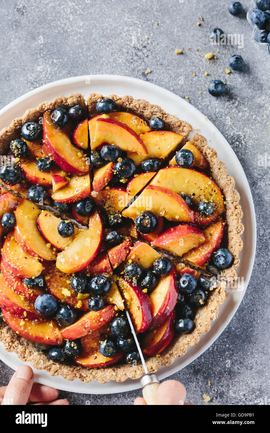 A woman is slicing a peach and blueberry tart with a knife photographed from the top view. Closer View. - Stock Image