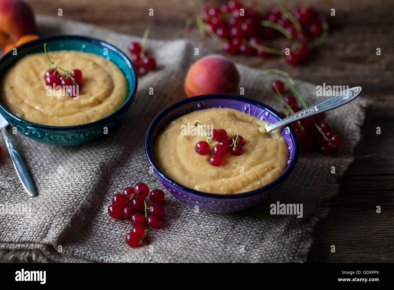Apricot vanilla millet pudding in two small bowls and topped with red currant - Stock Image