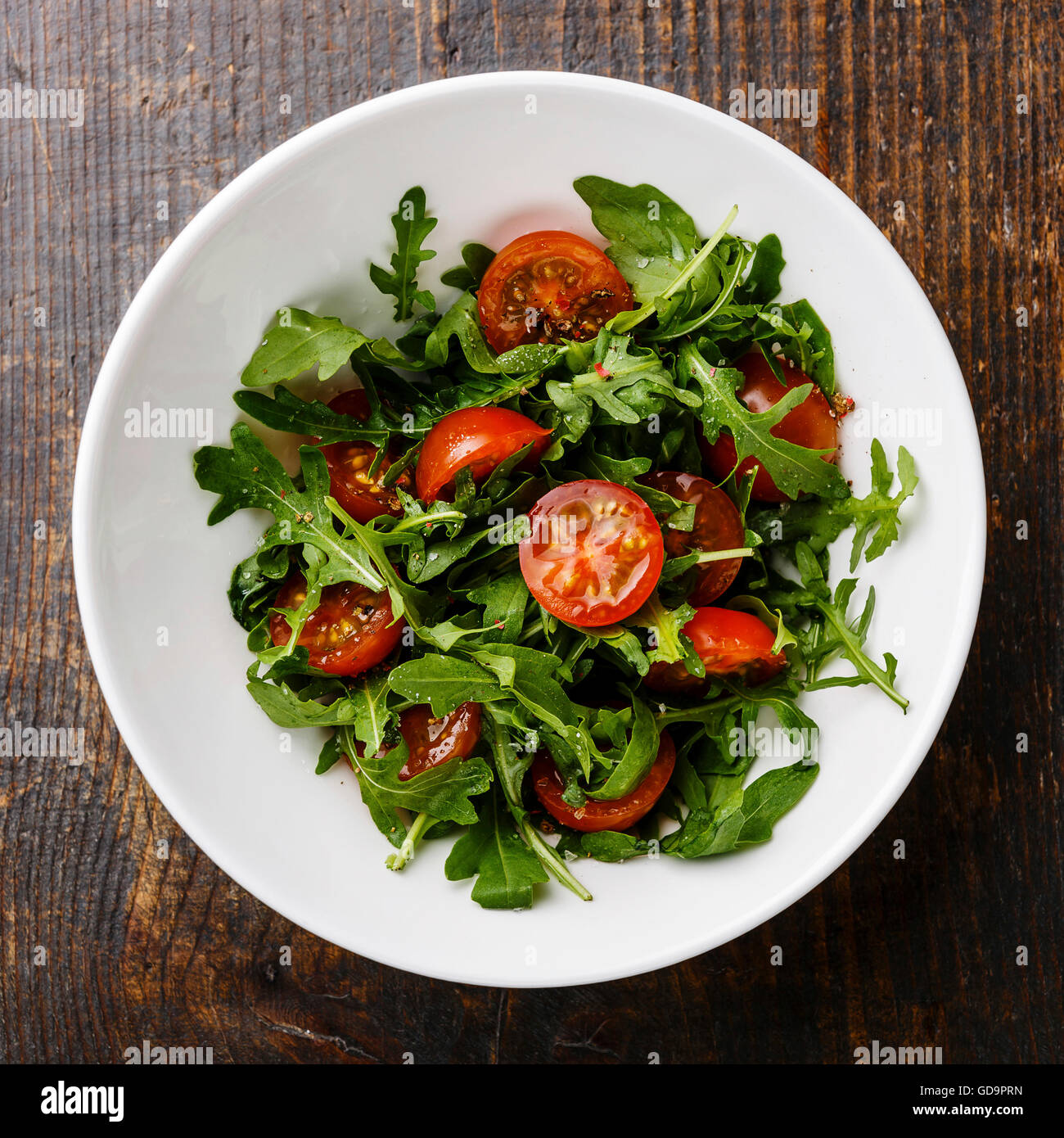 Salad with Cherry tomatoes and Arugula in white bowl on wooden background Stock Photo
