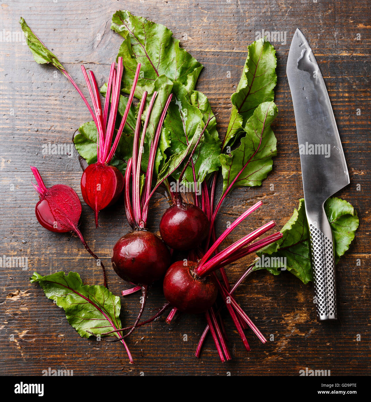 Red Beetroot with herbage green leaves and kitchen knife on wooden background - Stock Image