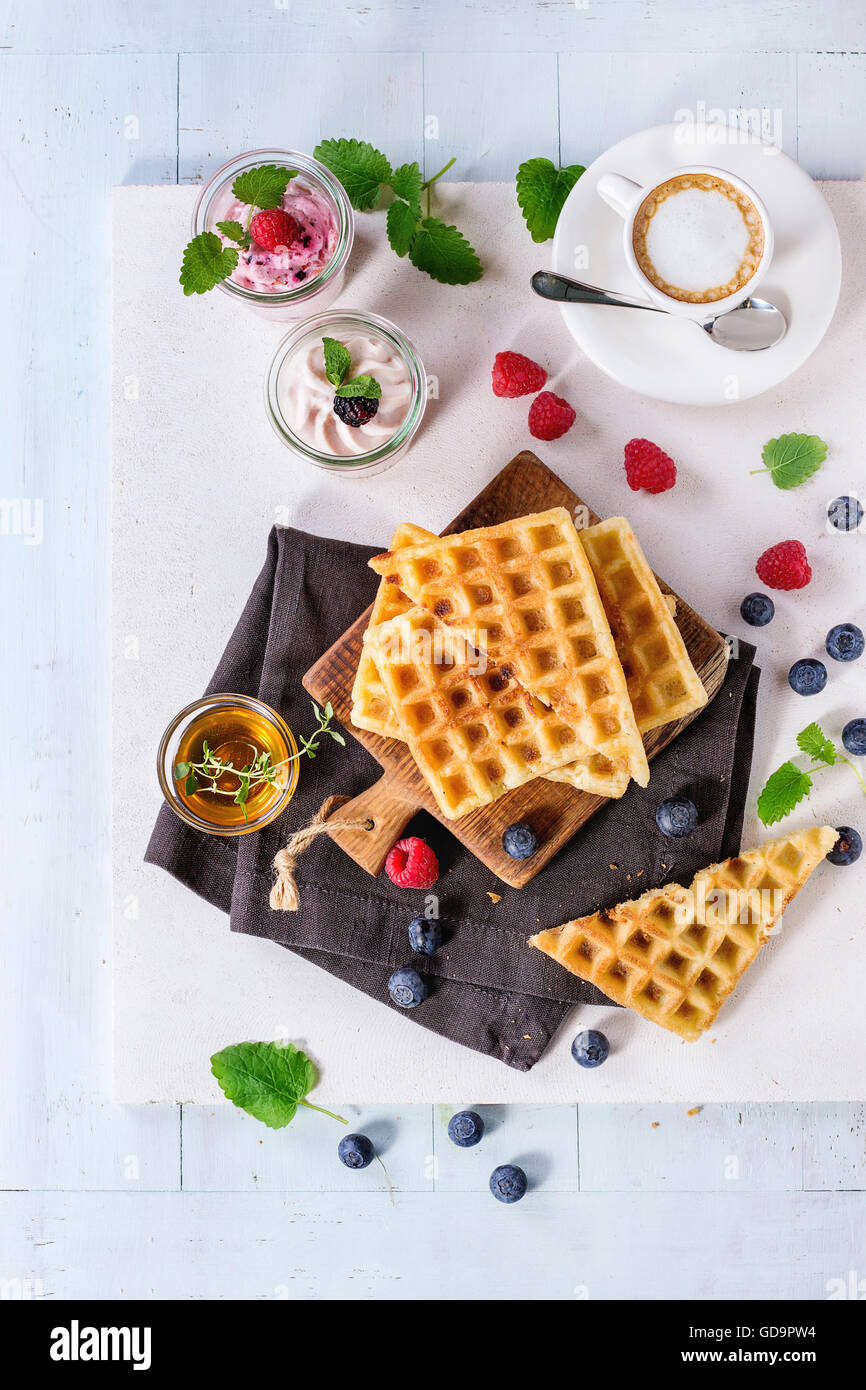 Breakfast theme with belgian waffles, berries, honey, cup of coffee and yogurt, served on wooden table with white - Stock Image