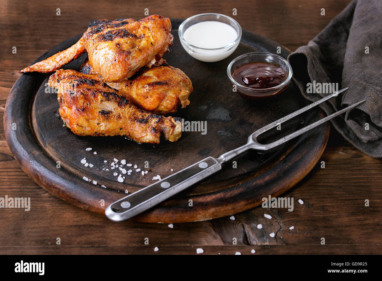 Grilled BBQ chicken meat wings and legs served on round wood chopping board with two sauces, salt and vintage meat Stock Photo