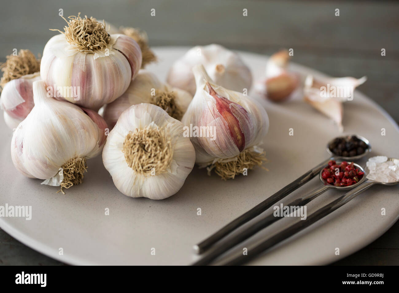 Plate of Garlic Blubs with Himalayan Pink Rock Salt and Pink and Black Peppercorns. - Stock Image