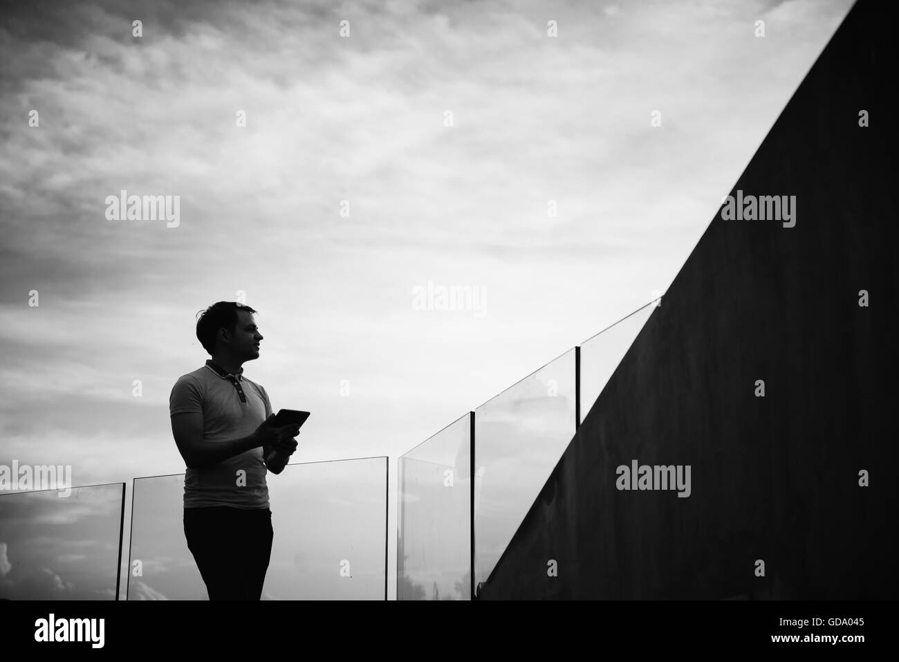 Silhouette of young business man using tablet outdoors Stock Photo