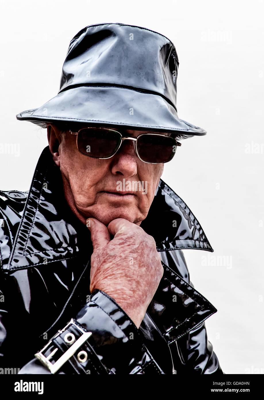 Menacing man in black pvc raincoat - Stock Image
