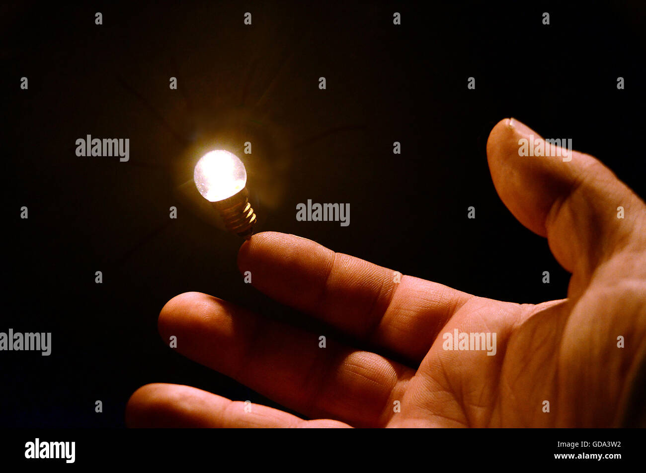 A light bulb seems to balance on a human finger. - Stock Image