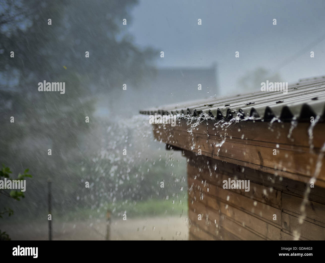 rain streams flowing from the roof - Stock Image