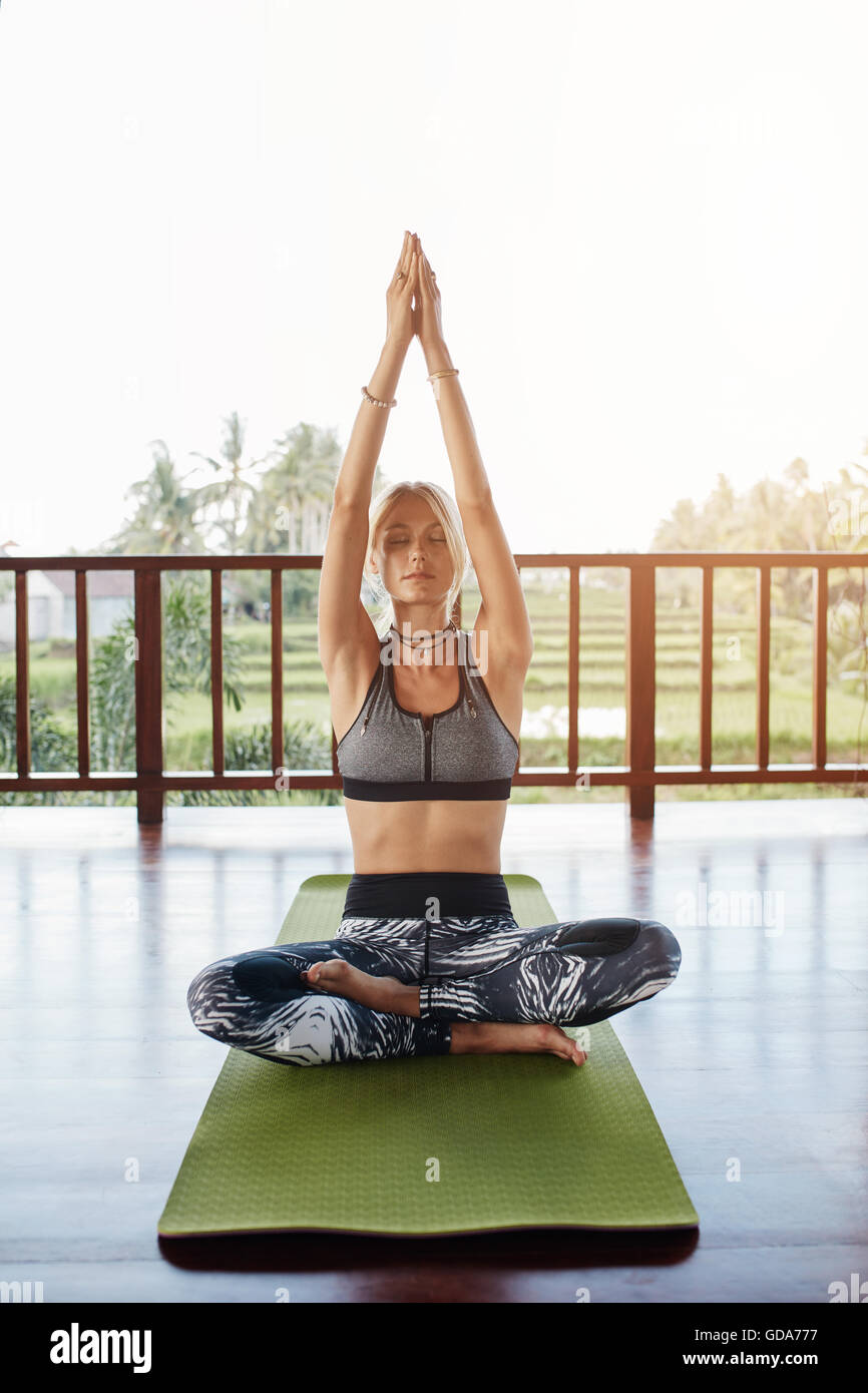 Caucasian woman practicing yoga at health center. Woman in yoga pose with eyes closed and hands joined while sitting - Stock Image