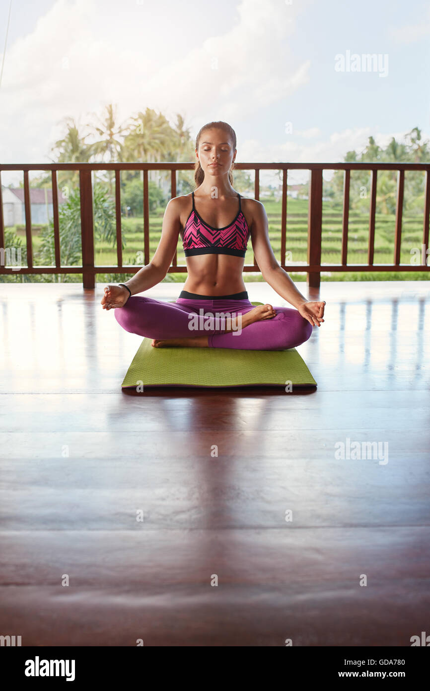 Vertical shot of female meditating in yoga class. Woman in yoga pose with eyes closed sitting on floor. - Stock Image