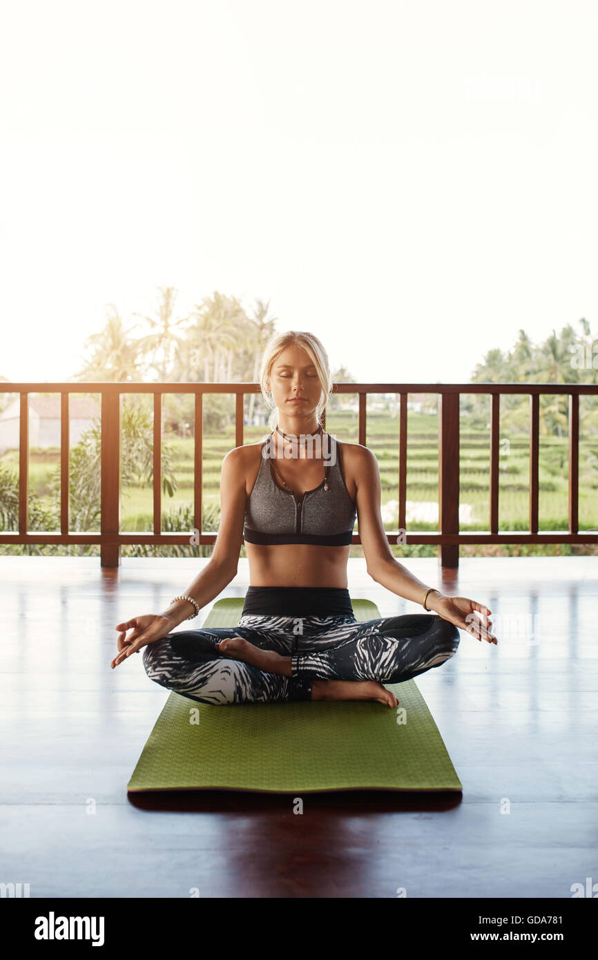 Shot of fit young female meditating in yoga class. Woman in yoga pose with eyes closed sitting on floor. - Stock Image