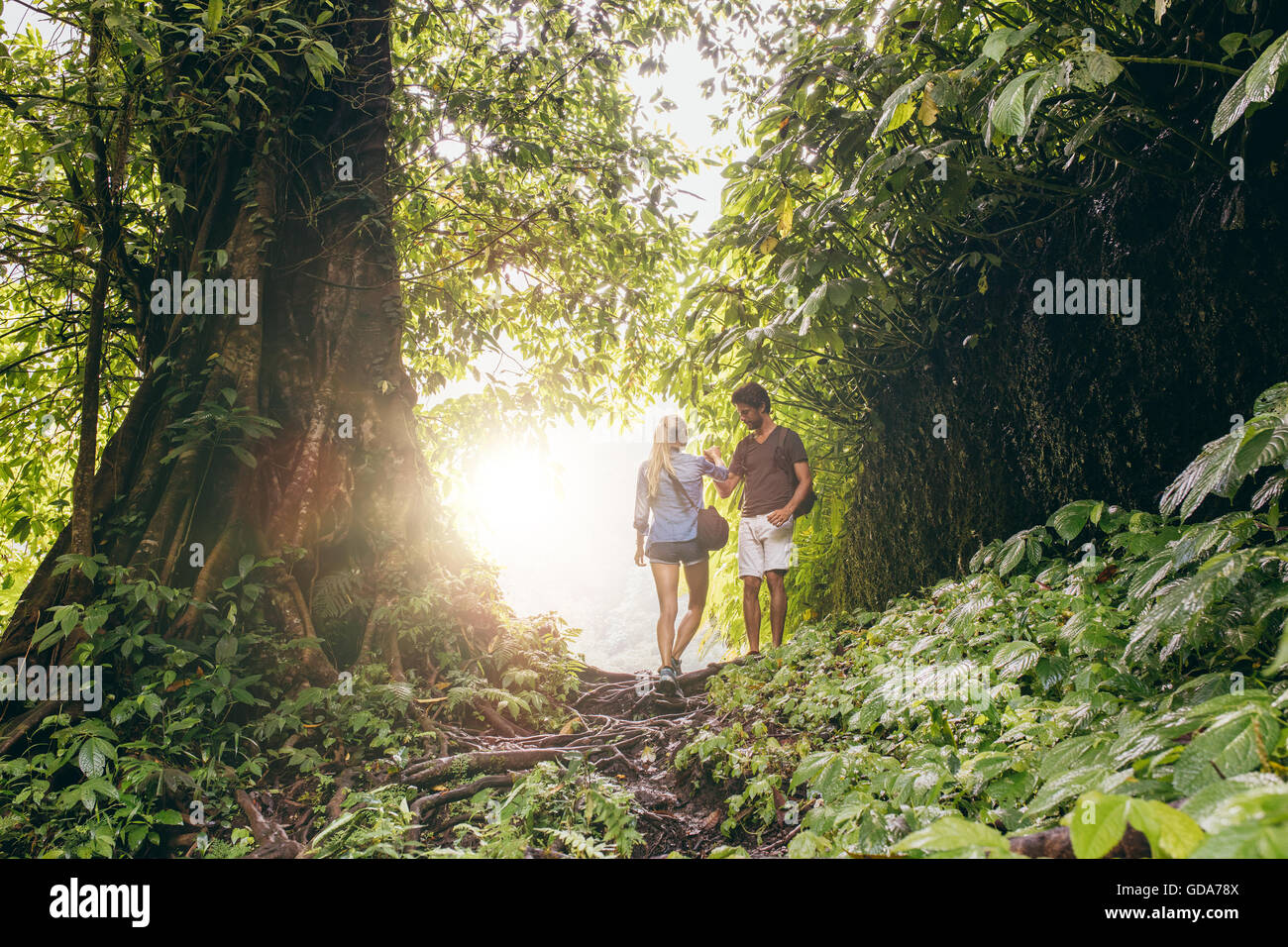 Young man and woman hiking in tropical jungle. Couple of hikers walking along forest trail. Stock Photo