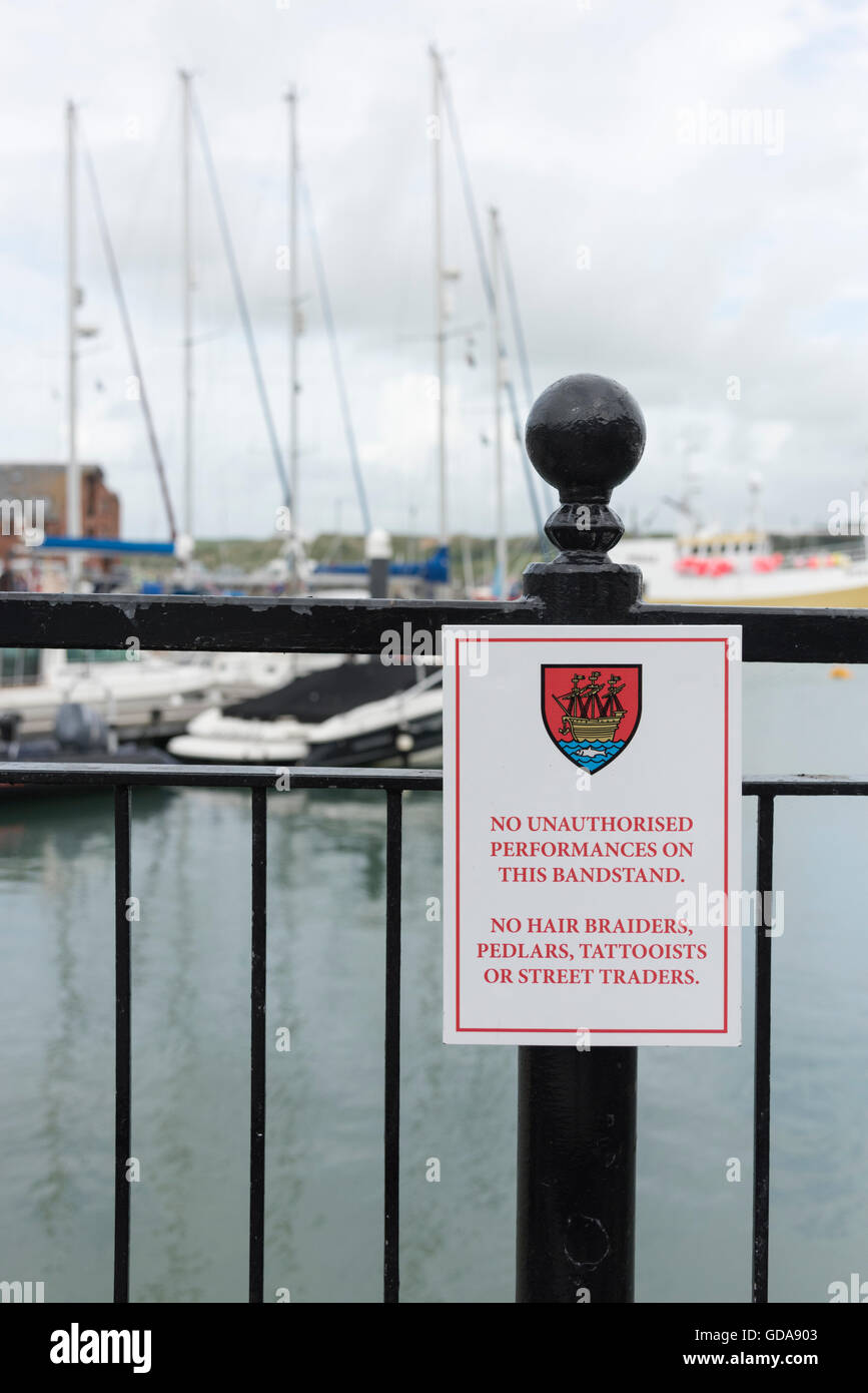 A sign on the harbour at Padstow UK prohibiting busking and street trading and traders - Stock Image
