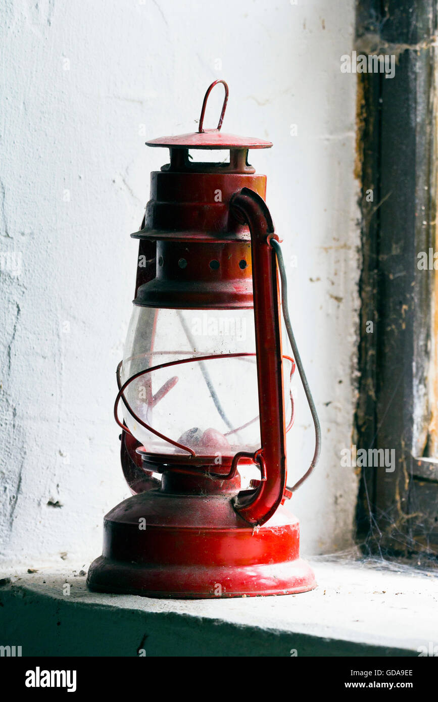 Old oil lamp sitting on a window sill - Stock Image
