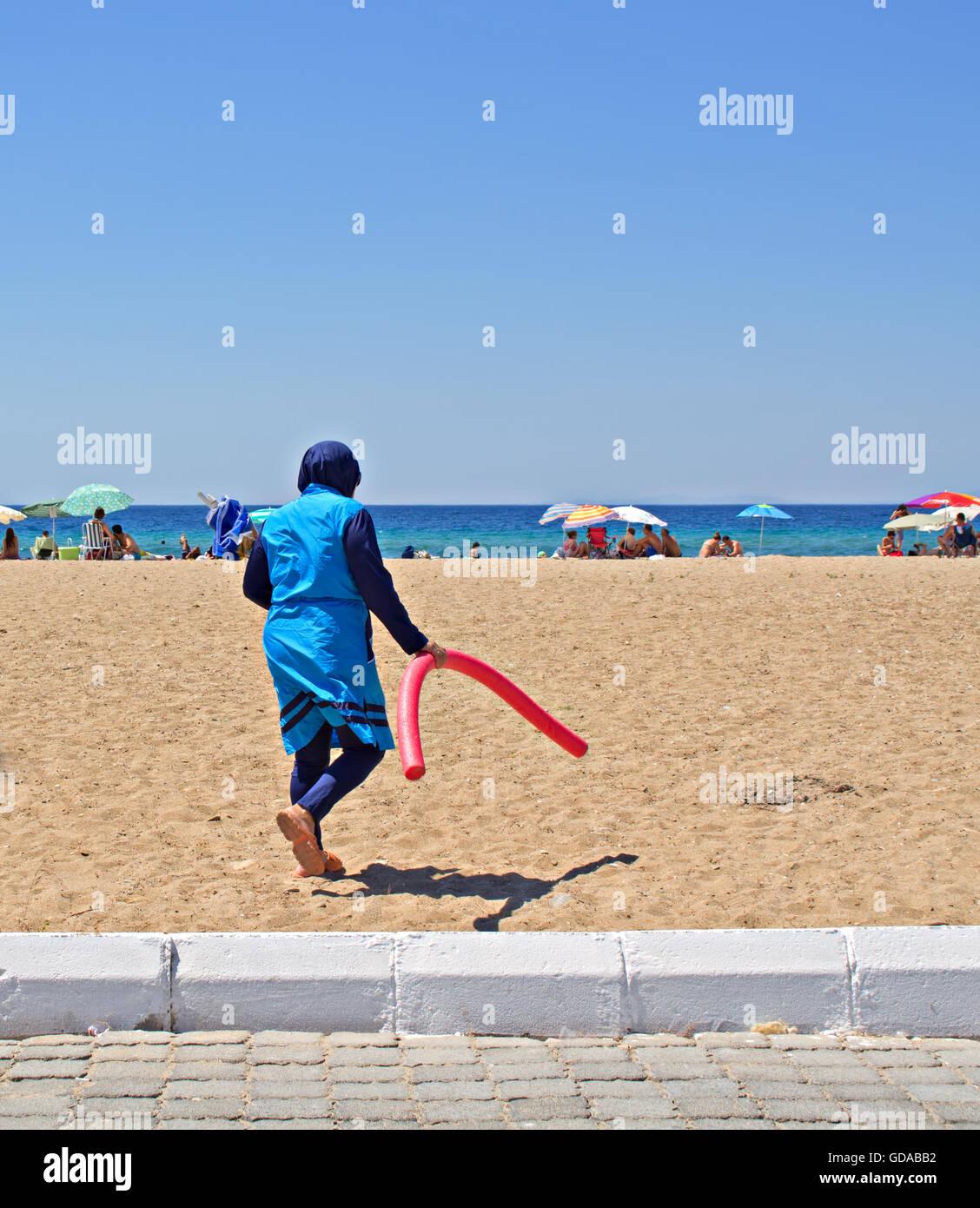Muslim woman walking on the beach in her Birkini swimwear - Stock Image