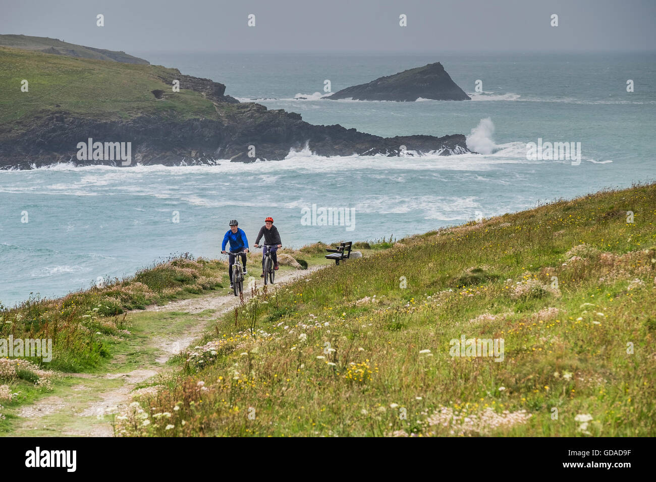 Two mountain bikers cycling along a footpath on East Pentire Headland in Newquay, Cornwall. - Stock Image