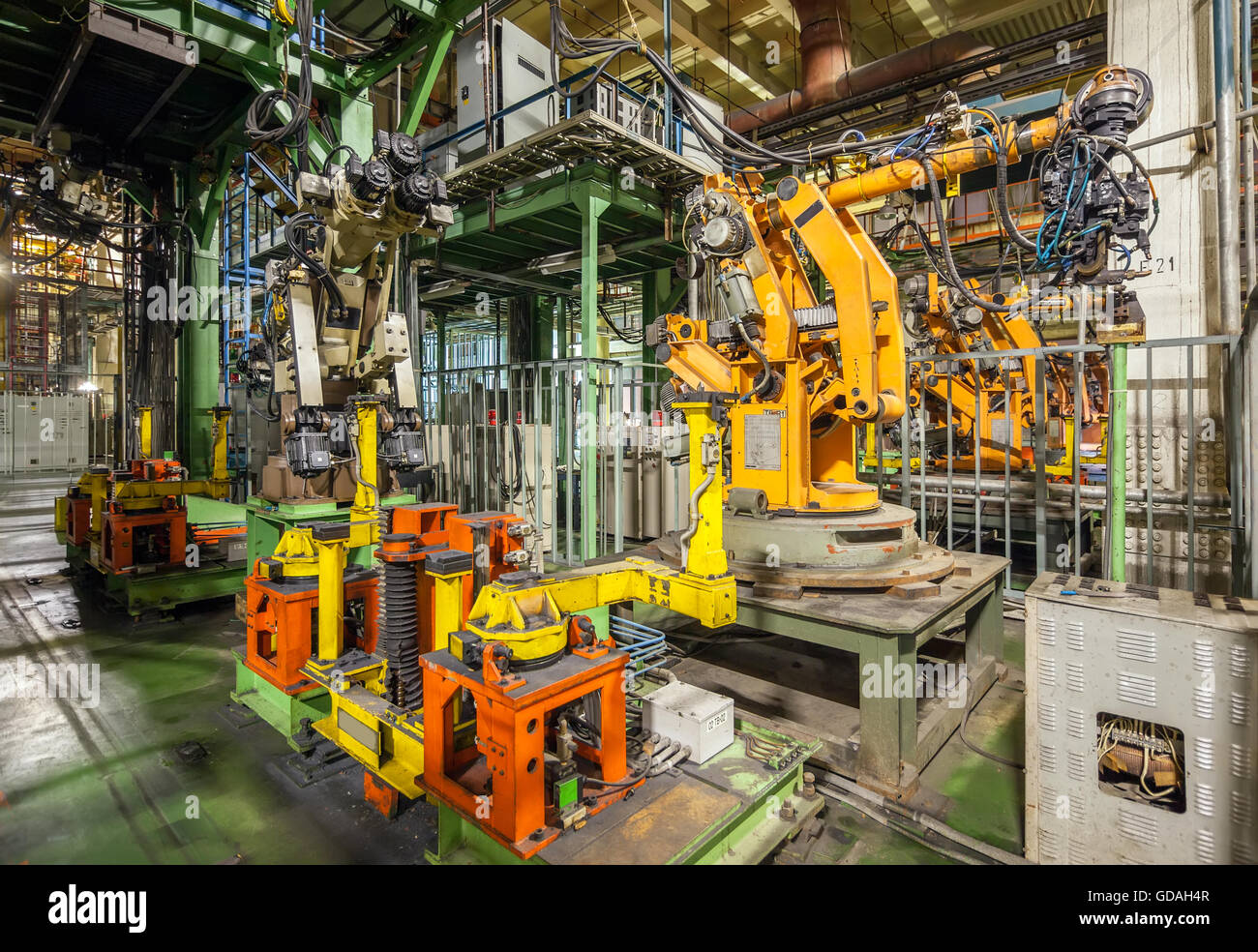 Bankrupt and abandoned automobile plant. Yellow robots welding cars in a production line Stock Photo