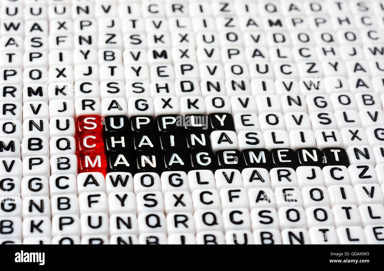SCM Supply Chain Management  written on black and white  dices Stock Photo