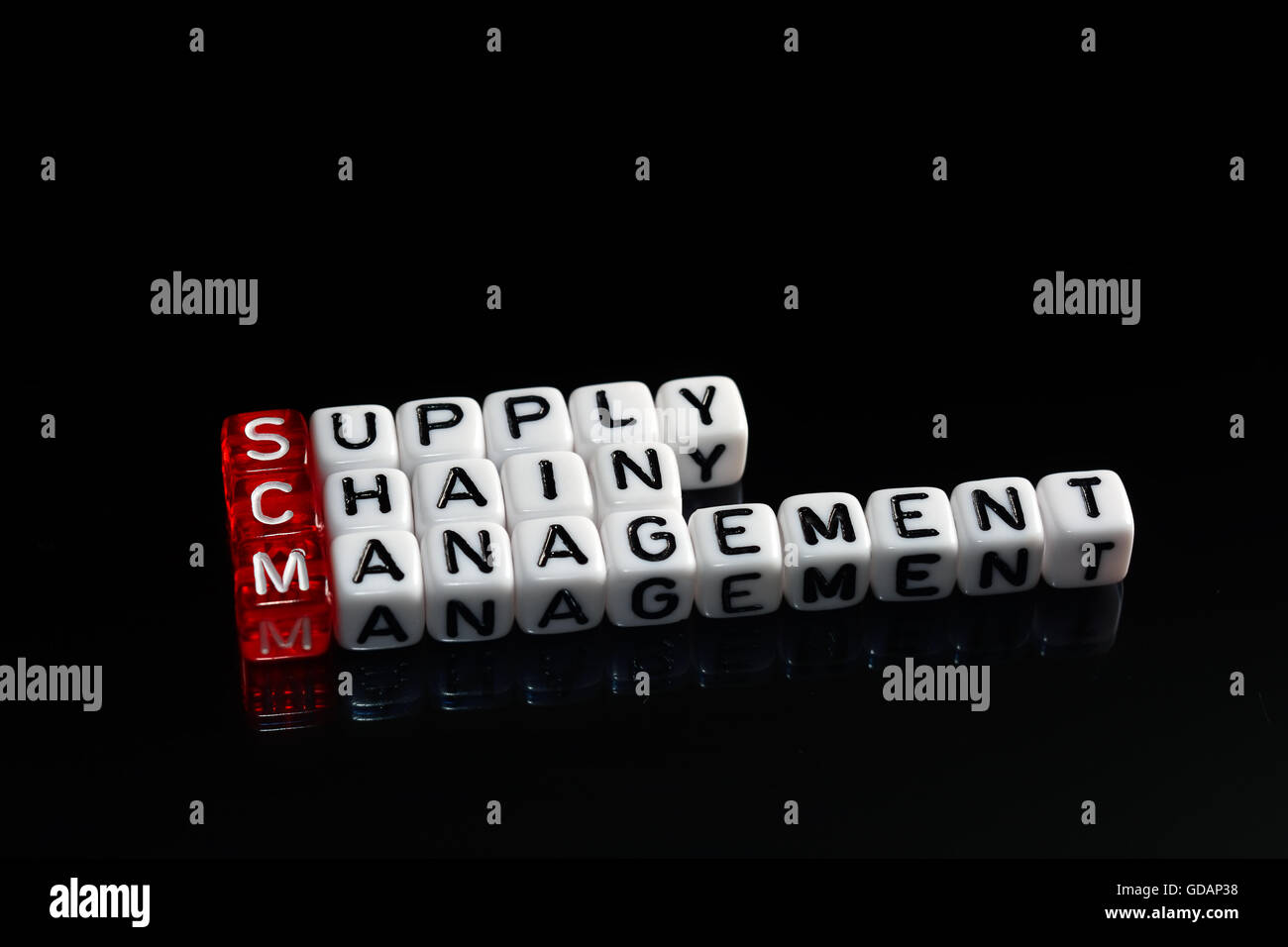 SCM Supply Chain Management written on dices on black background Stock Photo