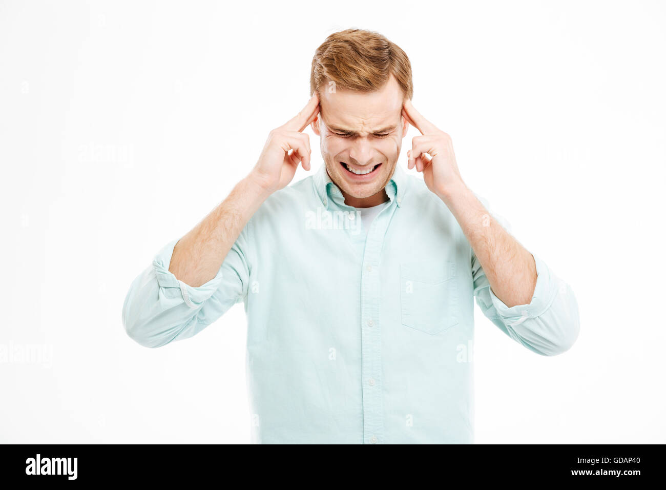 Stressful depressed blond man touching his temples and having headache over white background - Stock Image