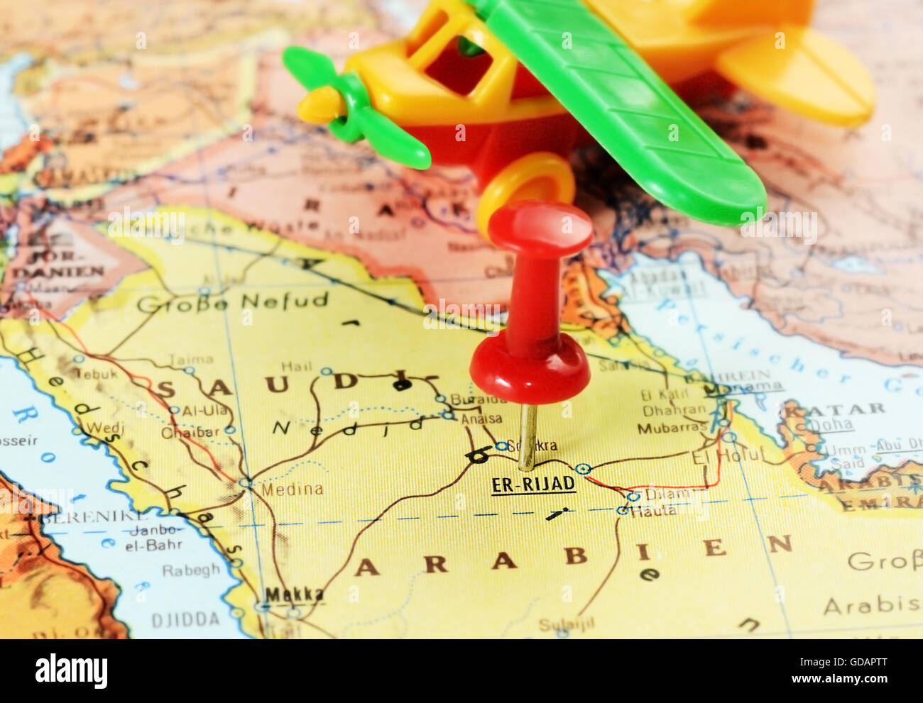 5d418ffe Close up of Er Riyadh,Saudi Arabia map with red pin and airplane toy -  travel concept