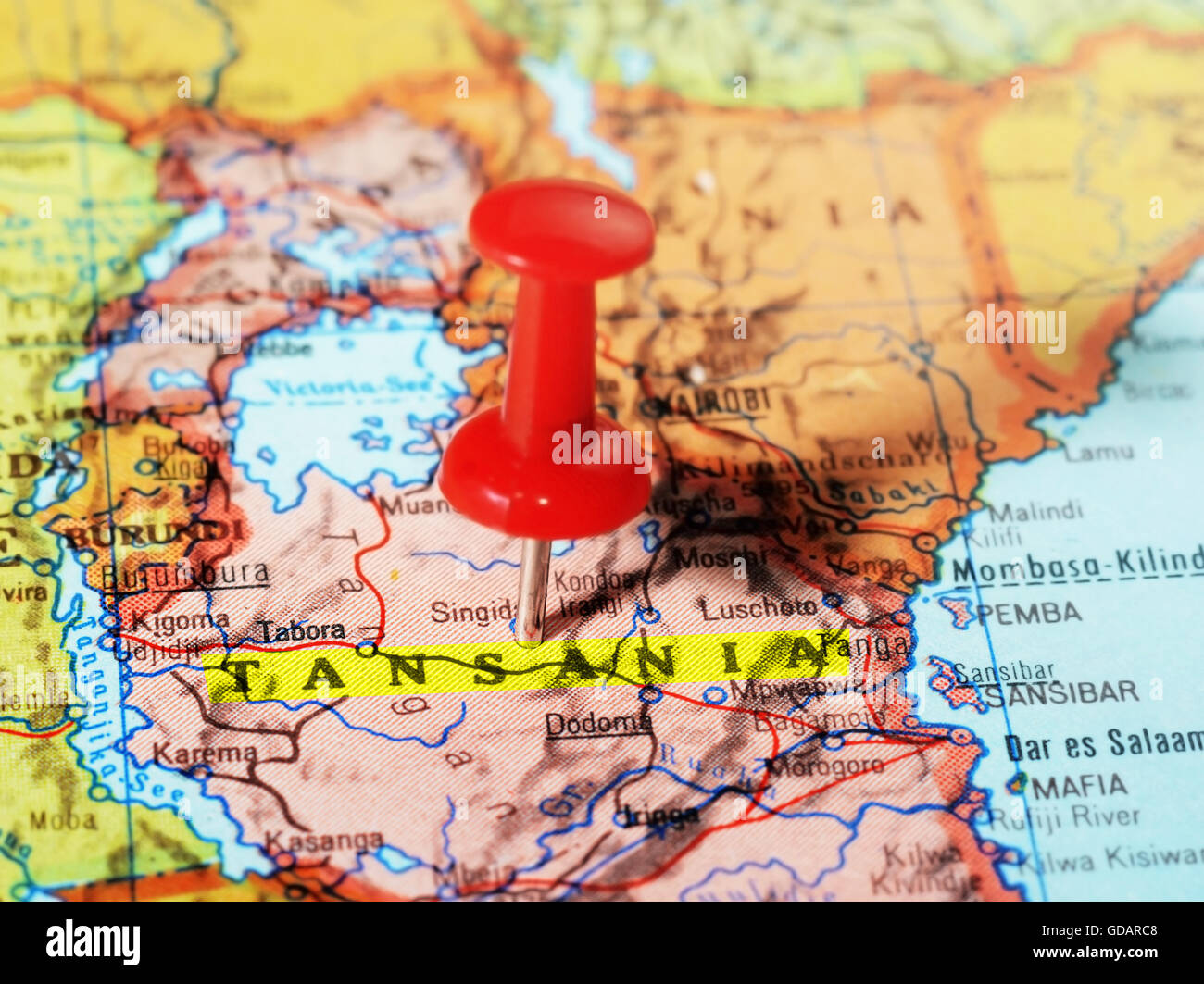 Close-up of a red pushpin on a map of  Tansania  Africa - travel concept - Stock Image
