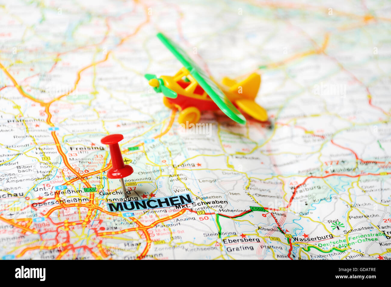 Close up of Munich Germany map with red pin and airplane toy Stock