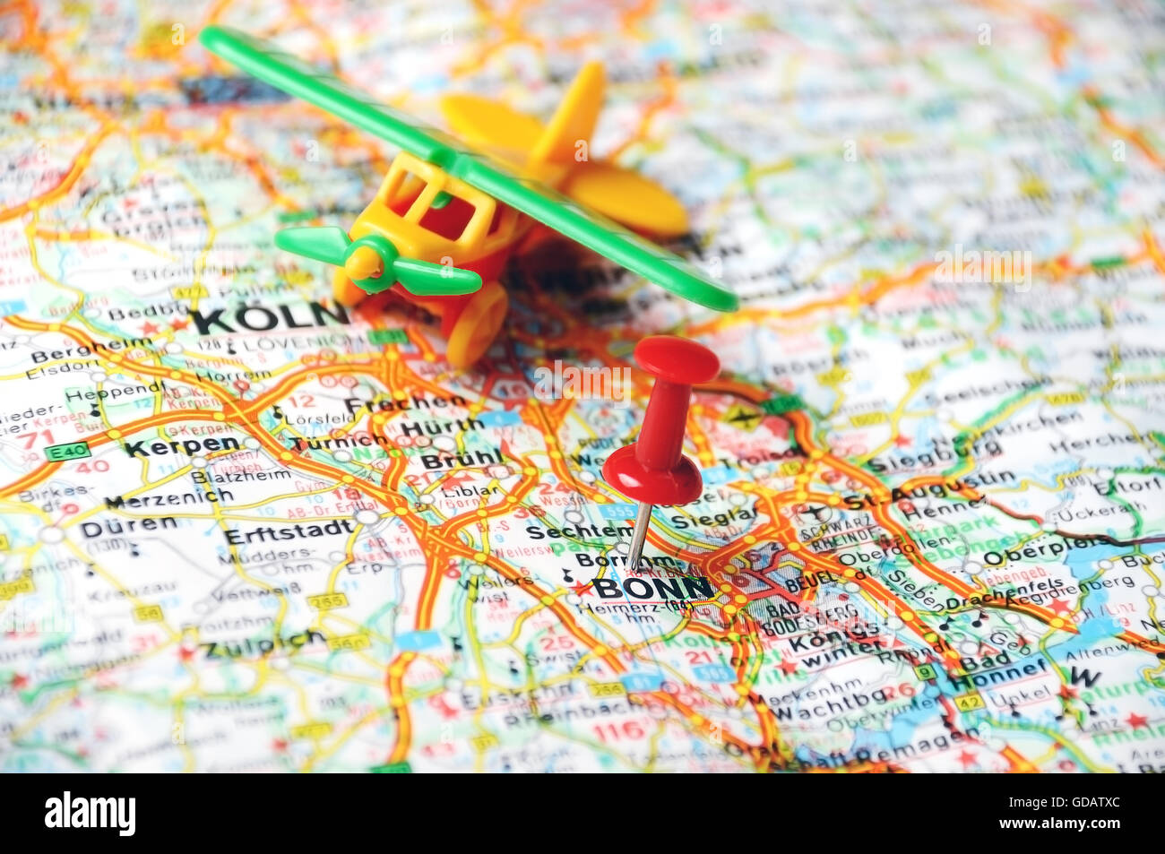 close up of bonn germany map with red pin and airplane travel concept