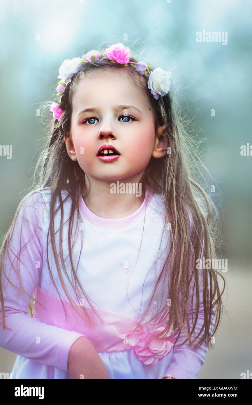 portrait of the small beautiful girl looking in distance - Stock Image