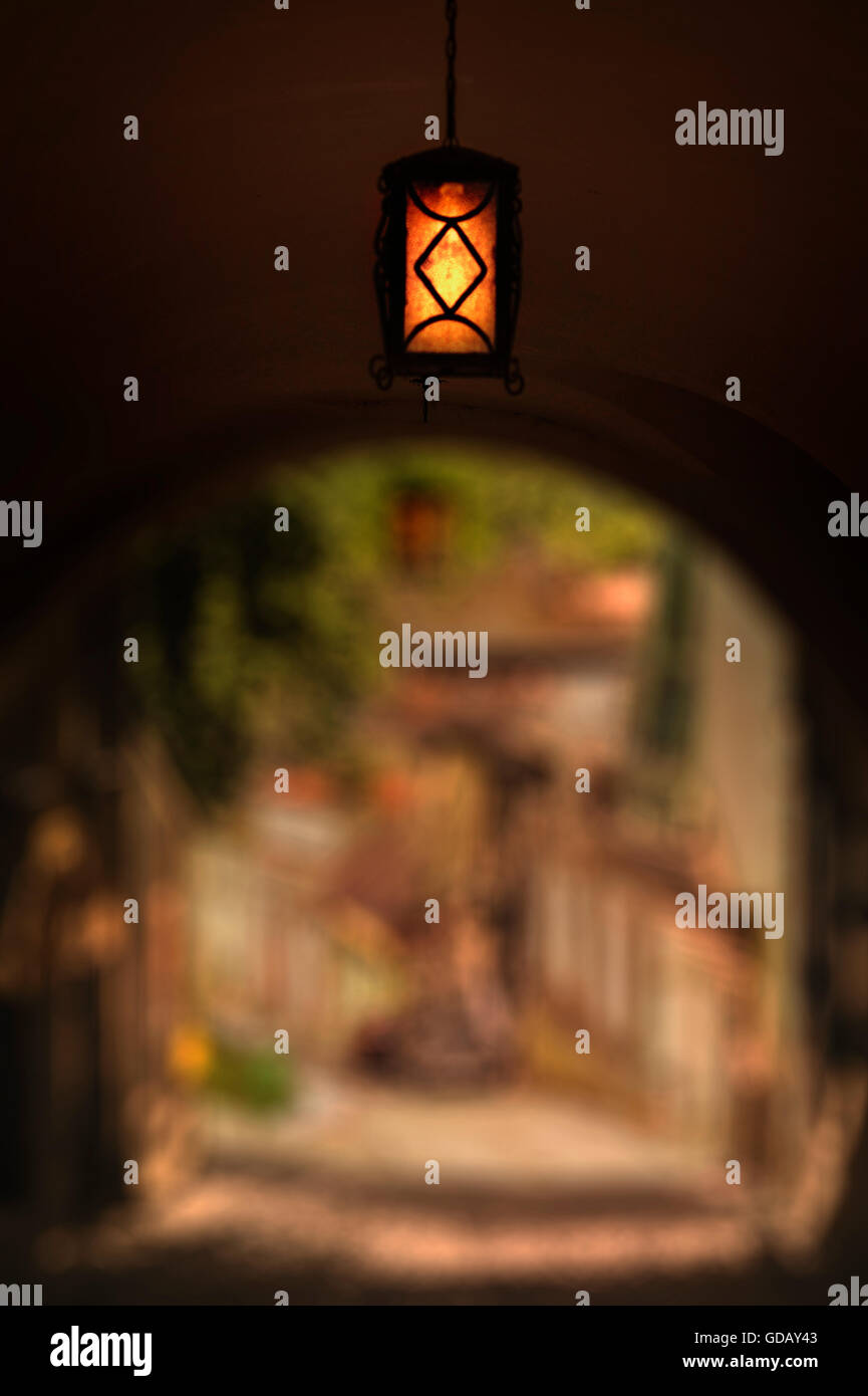 passing tunnel with a lamp in old town - Stock Image