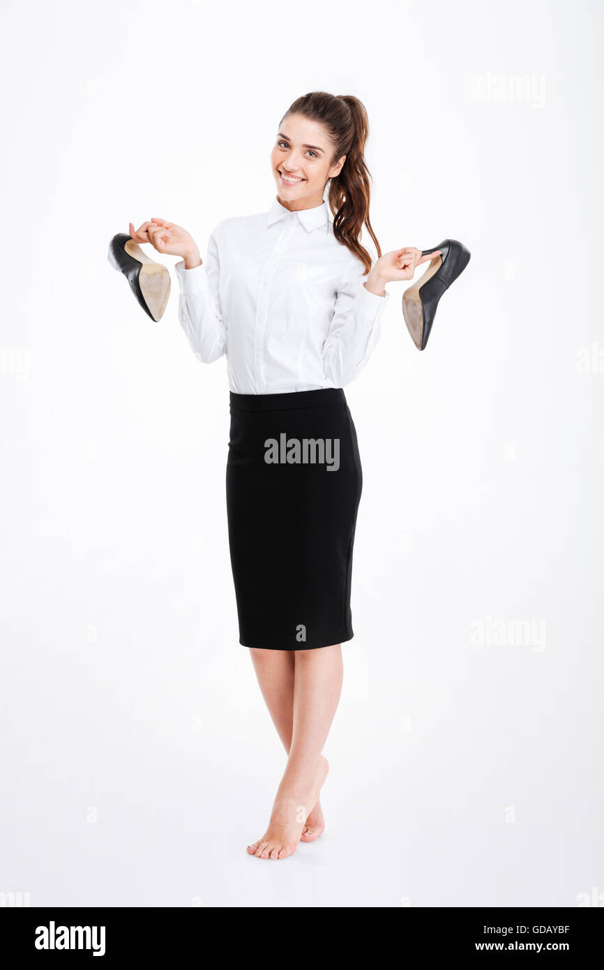 Full length of cheerful pretty young businesswoman standing and holding high heels shoes over white background - Stock Image