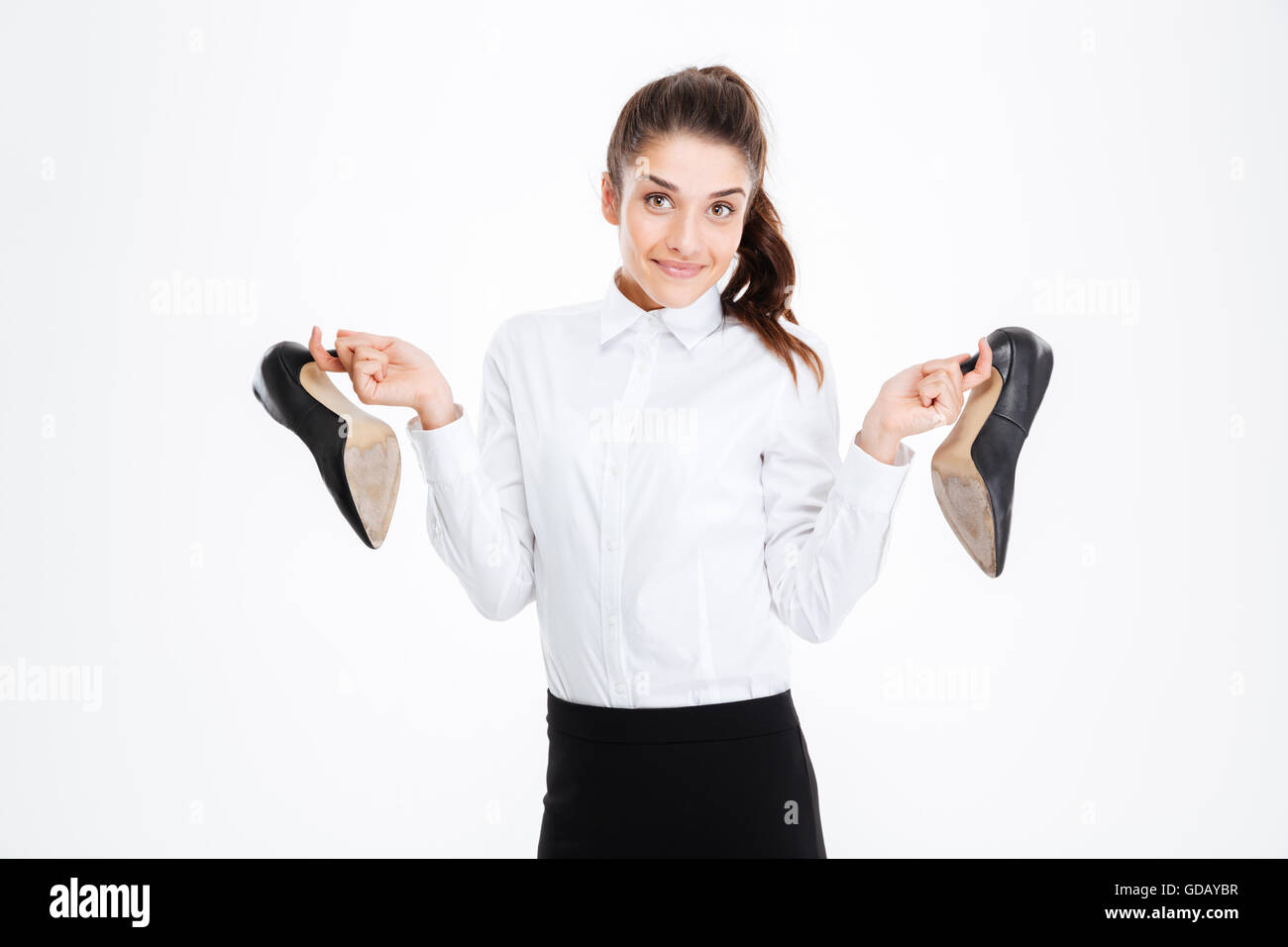 Happy cute young businesswoman holding high heels shoes over white background - Stock Image