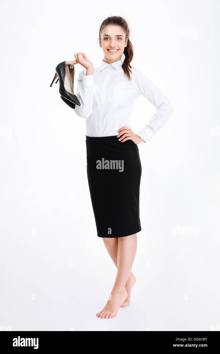 Smiling lovely young businesswoman standing barefoot and holding high heels shoes over white background - Stock Image
