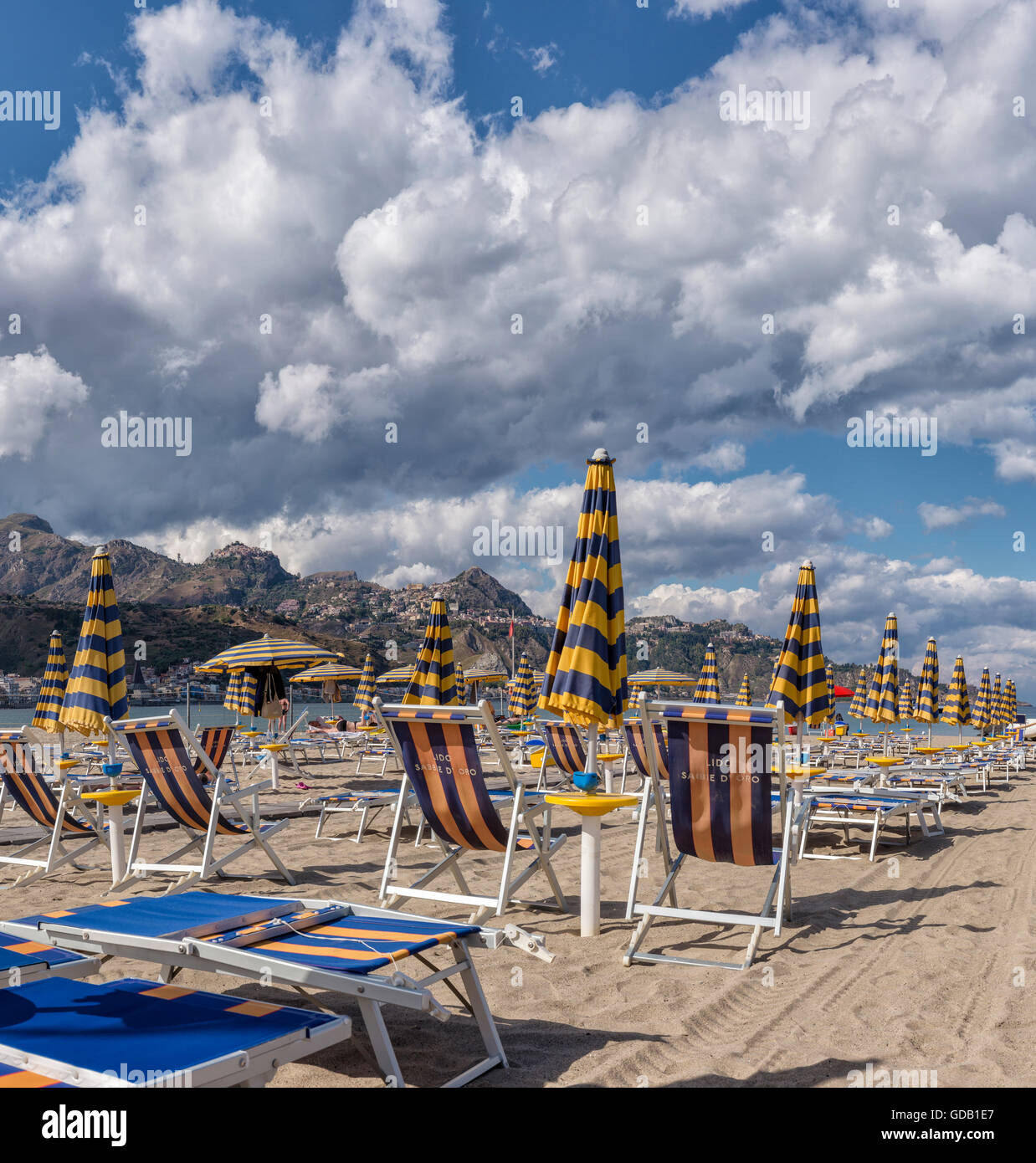 Deck chairs and sunshades,view towards Taormina on a mountain ridge - Stock Image