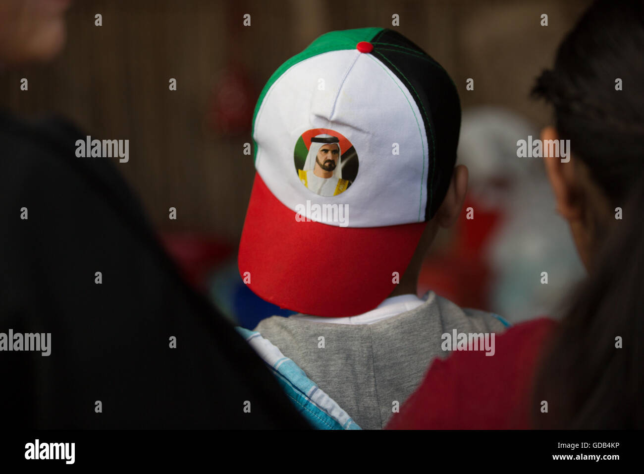 A boy wears a cap with the Emirati flag on it backwards for National Dress.  A photograph of Sheikh Mohammed bin Rashid Al Maktoum 96681838058