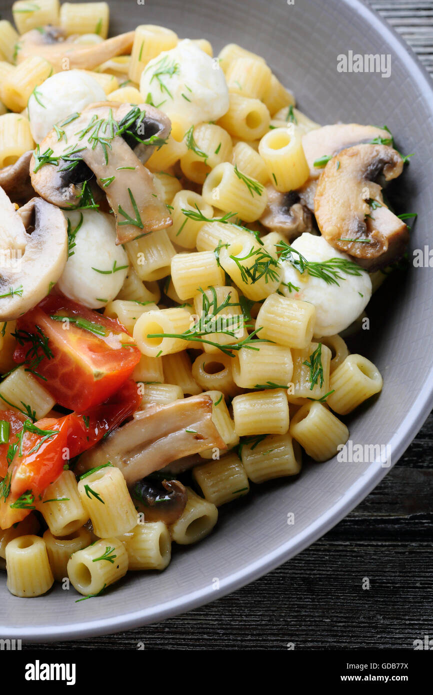 fresh pasta with roasted tomatoes in bowl, food close-up - Stock Image