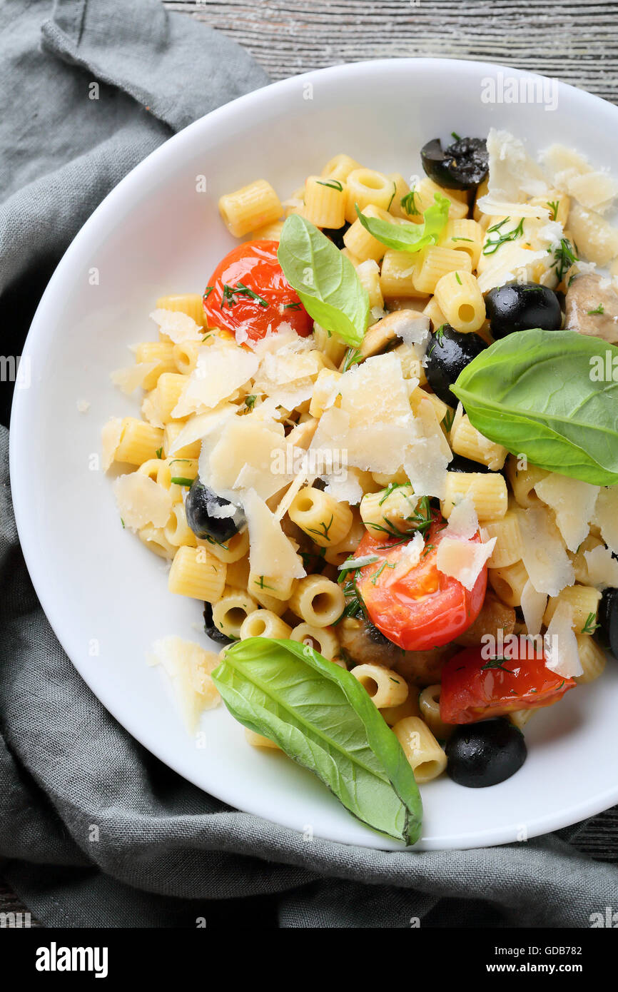 italian pasta with cheese and basil in white bowl, food close-up - Stock Image