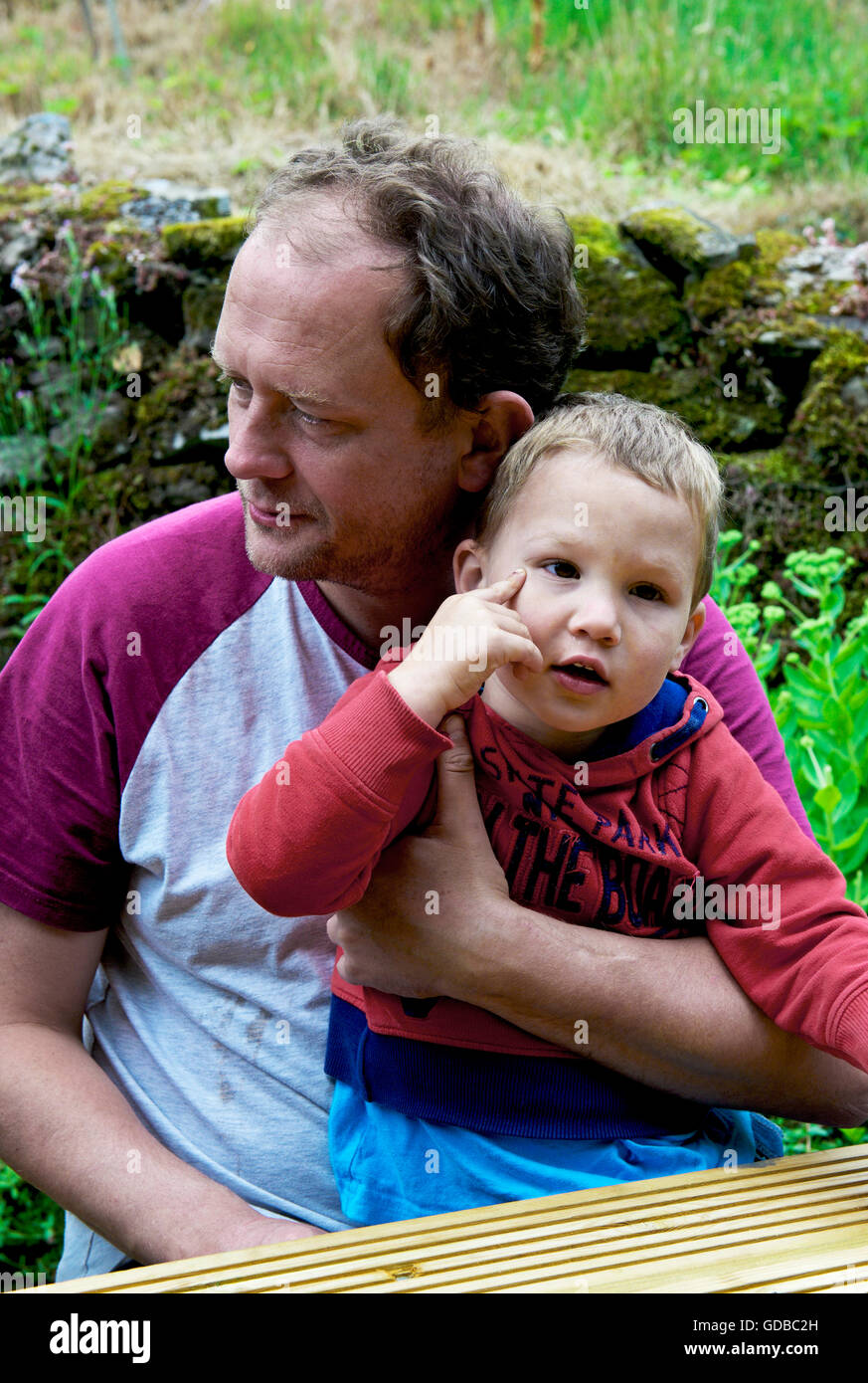 Man sitting with two year old son, UK - Stock Image