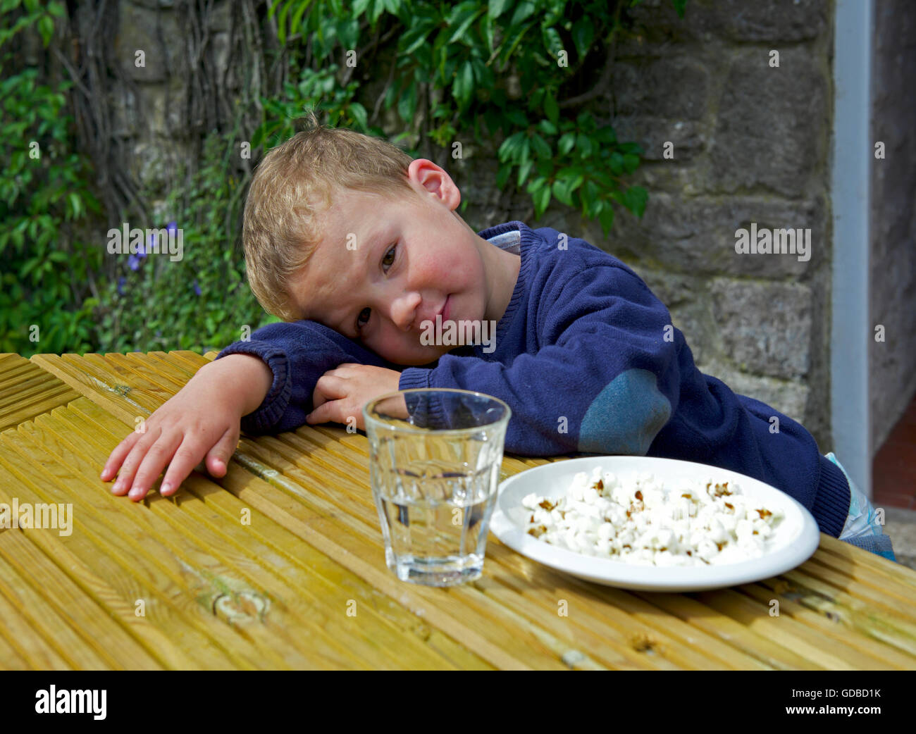 two year old boy sitting at a table - Stock Image