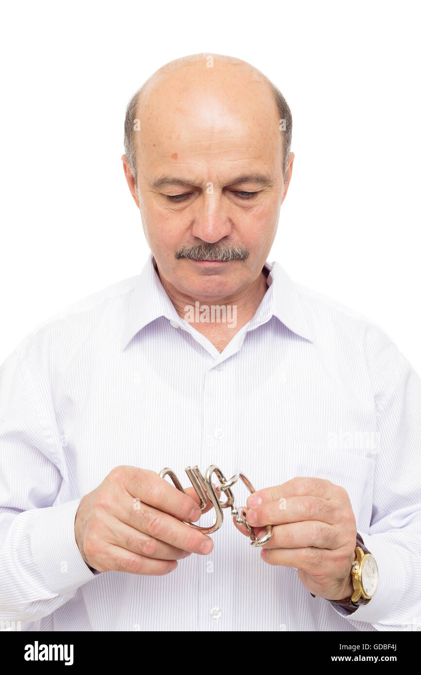elderly man tries to solve a complex puzzle, jigsaw - Stock Image