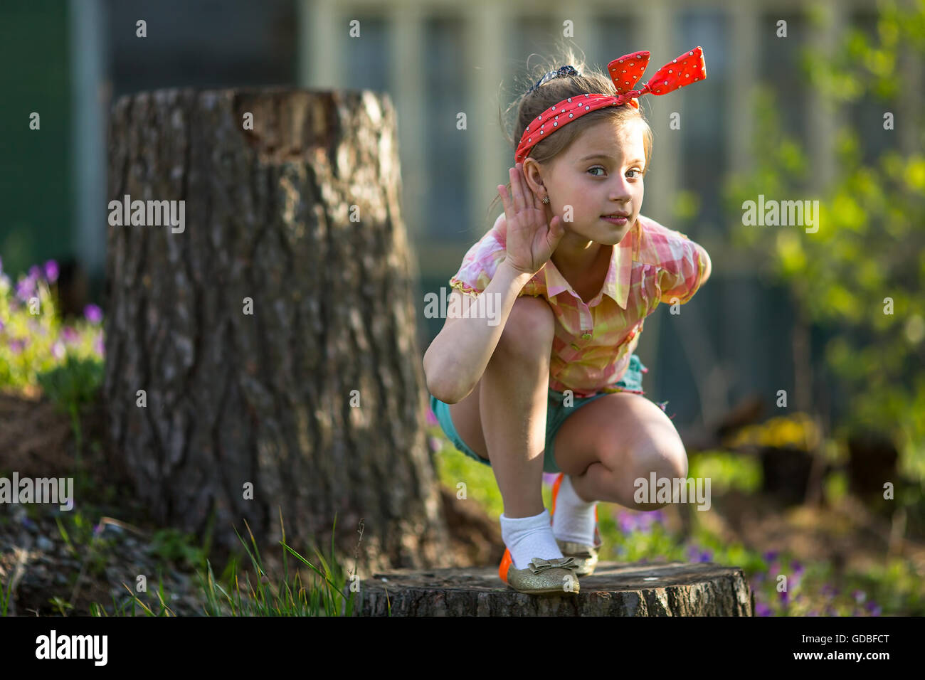 Little naughty girl outdoors, makes the gesture of listening. Stock Photo
