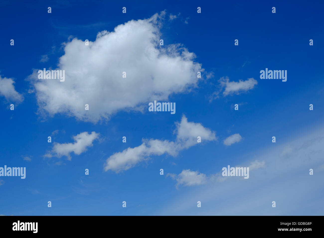 Fluffy clouds in a blue sky - Stock Image