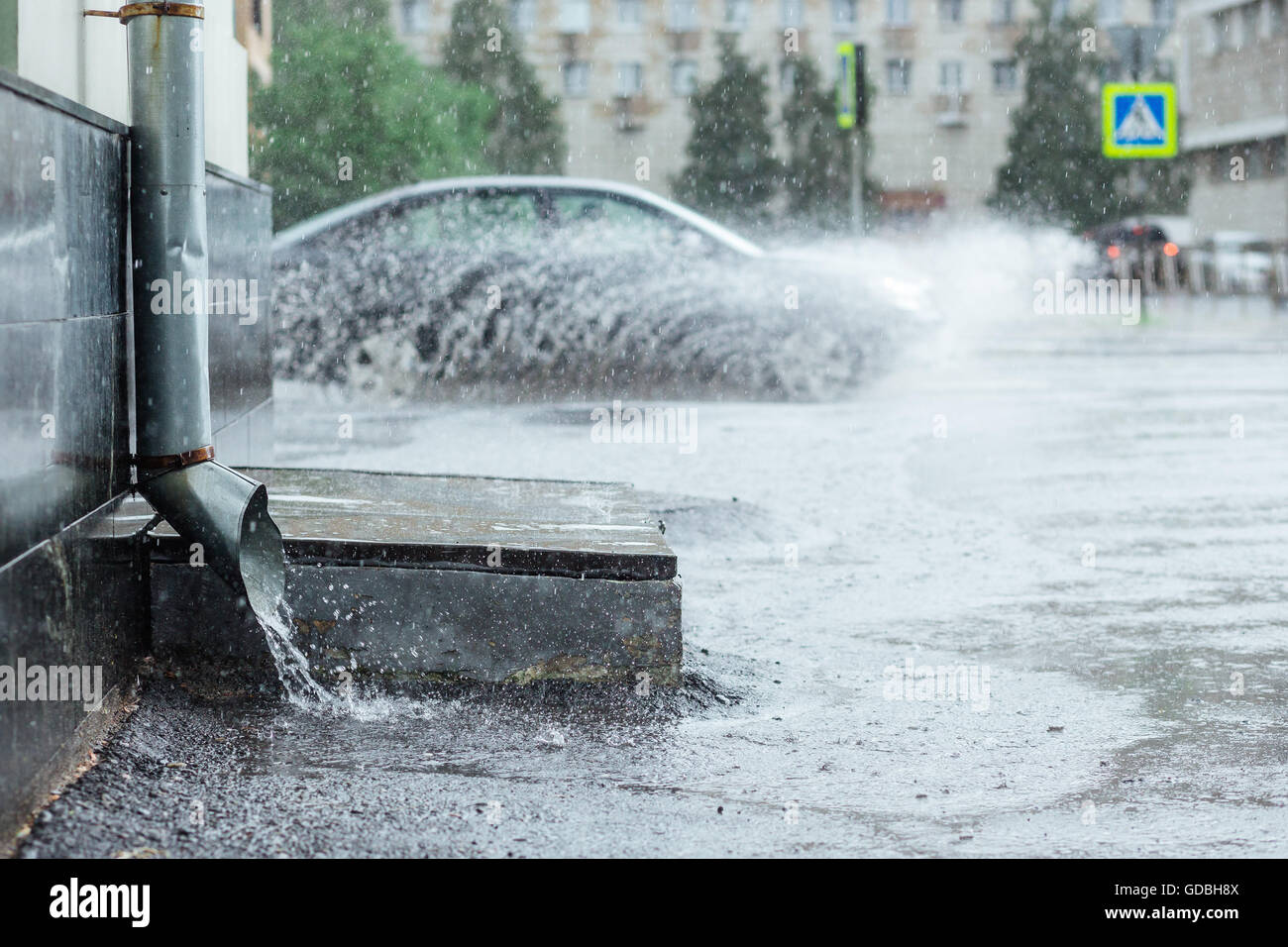 Rain water flowing from metal drainpipe during a flood. splashes of cars background. concept  protection against - Stock Image