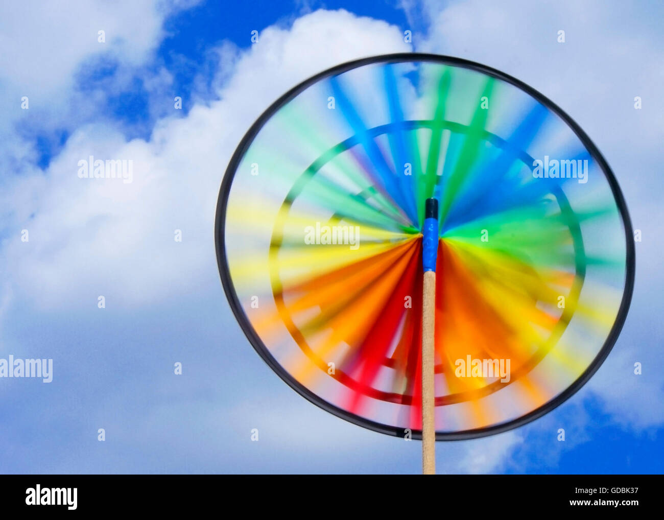 Rainbow colored pinwheel rotates in the summer sky. - Stock Image