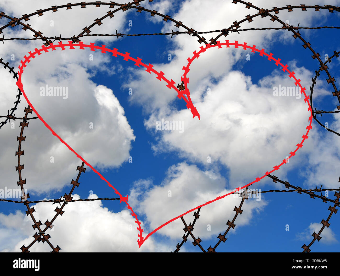 Natural heart shape (digitally coloured red) in a barbed wire fence on sky background. Love, freedom, peace, hope - Stock Image