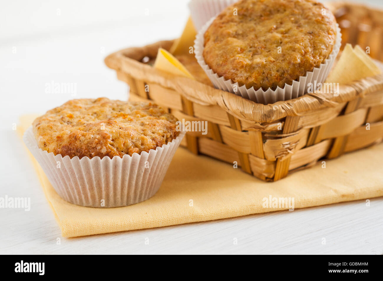 bright fragrant pumpkin cup cakes, muffins in a basket. - Stock Image