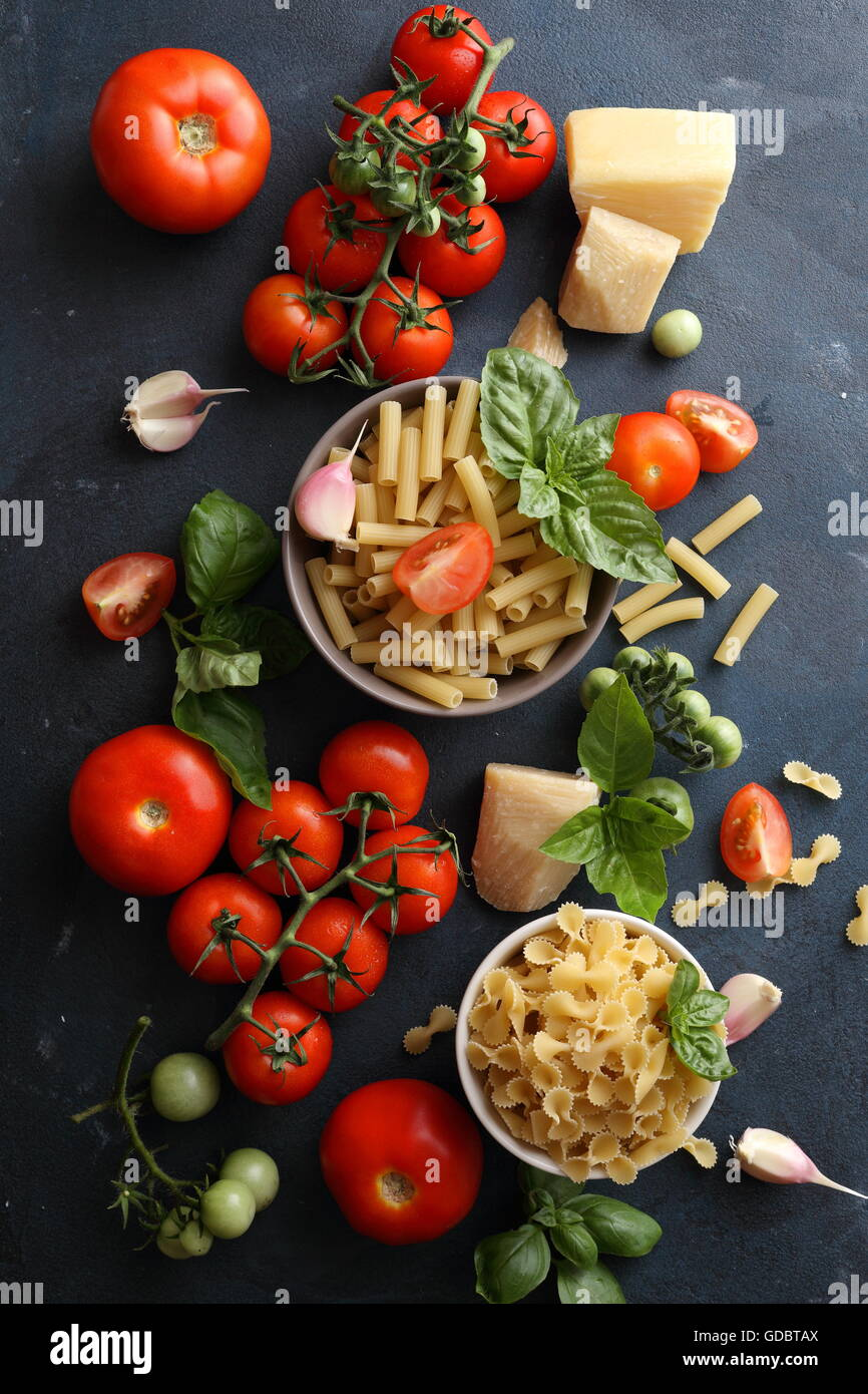 raw pasta and tomatoes on slate - Stock Image