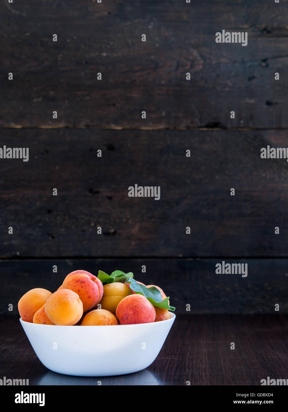 bowl with apricots on a wooden background. - Stock Image
