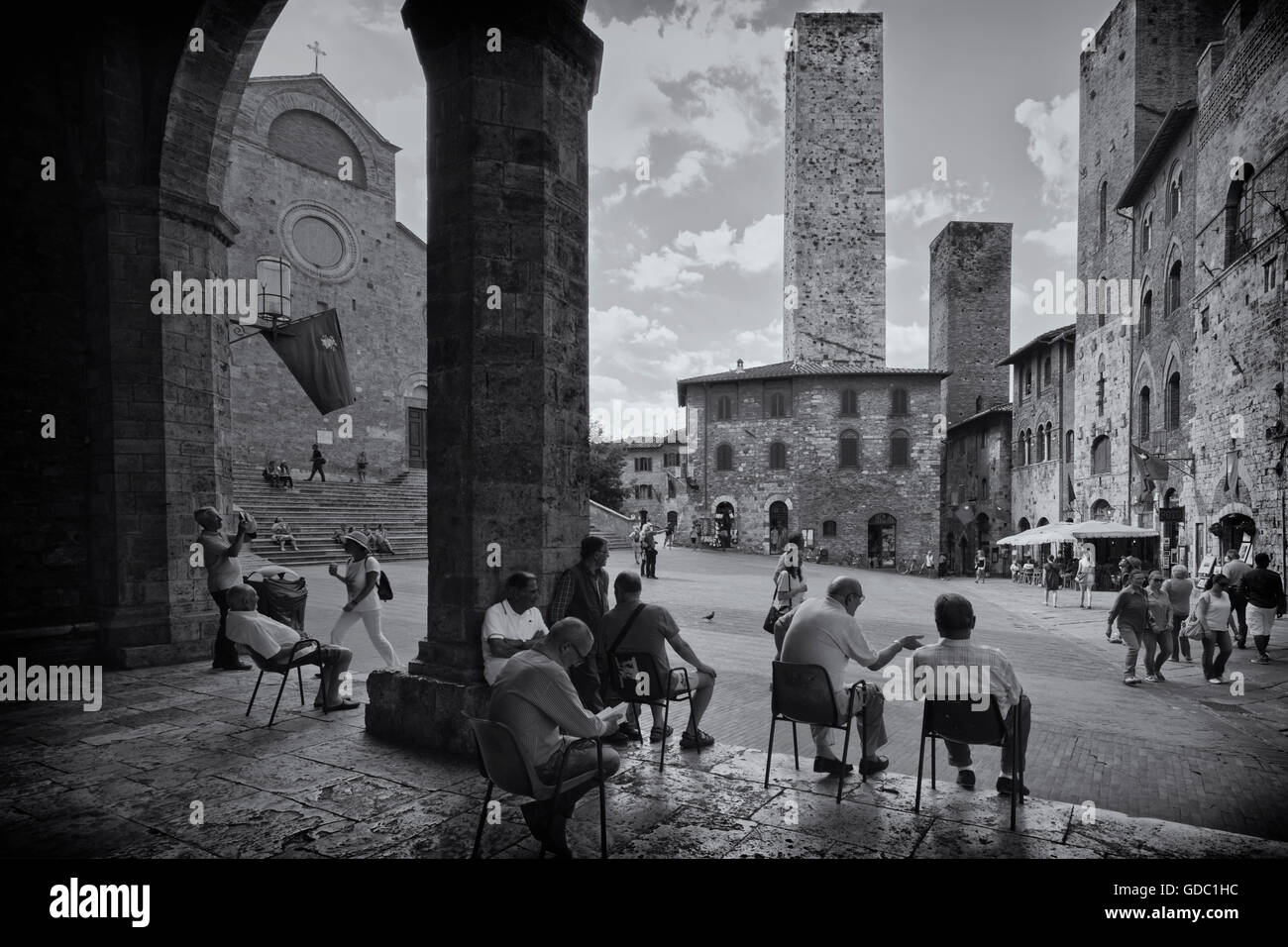San Gimignano, Siena Province, Tuscany, Italy.  Locals relaxing in Piazza del Duomo. - Stock Image
